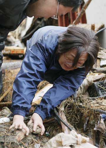 : Yoshie Murakami cries as she holds a hand of her dead mother in the rubble near the spot where her home used to be Wednesday, March 16, 2011 in Rikuzentakata, Iwate Prefecture. Murakami&#39;s 23-year-old daughter is still missing, Kyodo said.  <span class=meta>(&#40;AP Photo&#47;Kyodo News&#41;)</span>